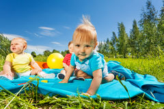 Positive cute toddlers sit on blanket in field royalty free stock photos