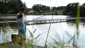Positive dad and son with rod angling at pond stock video footage
