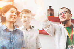 Positive delighted boys watching interesting experiment Royalty Free Stock Images
