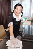 Positive delighted chambermaid wiping the table. Absolutely spotless. Positive delighted professional chambermaid holding a duster and leaning over the table Stock Photos