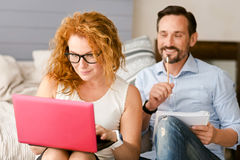 Positive delighted couple working at home Stock Images