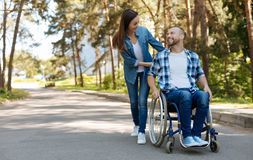 Positive delighted disabled man expressing positivity. Life continues. Kind brunette female person wearing casual clothes bowing her head while driving her Royalty Free Stock Image
