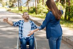 Positive delighted disabled man going to hug his friend. Time for hugs. Longhaired brunette female standing in semi position holding arms in the air while Royalty Free Stock Images