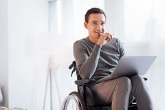 Positive delighted disabled man looking forward. Having secret. Enigmatical male keeping smile on his face and holding glasses in right hand while sitting on the Stock Photo
