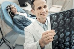 Positive delighted doctor looking at the X ray photo. Professional diagnostician. Positive smart delighted doctor looking at the X ray photo and being in a good Stock Image
