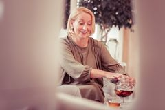 Positive delighted elderly female going to drink tea royalty free stock photos