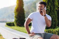 Positive delighted foreign man using telephone. Friendly talk. Handsome brunette keeping smile on his face and putting right hand on the pocket while looking Royalty Free Stock Photo