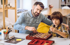 Positive delighted friends playing chess Stock Photography