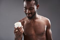 Cheerful handsome afro America man holding a cream jar stock photo