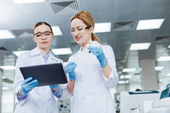 Positive delighted lab assistants looking downwards. Low angle. Pretty young scientists keeping smile on faces standing in the lab while going to examine blood royalty free stock photography