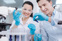 Positive delighted lab assistants testing new reagent. Wear uniform. Attractive male person keeping smile on his face and sitting close to his colleague while royalty free stock photos