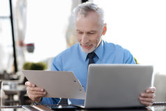 Positive delighted male person turning his head to folder Stock Image