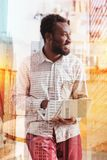 Positive delighted man holding laptop. Have a look. Cheerful bearded international office worker turning his head while looking aside and dreaming about vacation Stock Image