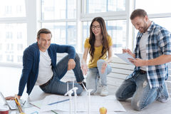 Positive delighted man sitting near his colleague. In team. Positive delighted pleasant men sitting near his female colleague and smiling while looking at the royalty free stock photography
