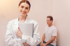 Positive delighted medical worker looking at camera. Follow me. Pretty brunette keeping smile on her face and embracing notebook while standing on the foreground stock images