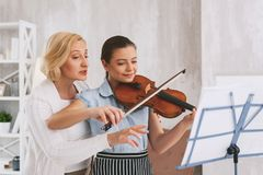 Positive delighted musician playing melody. I understand. Beautiful young female keeping smile on her face while learning new melody Royalty Free Stock Photos