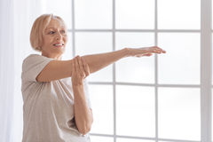 Positive delighted retired woman stretching her arms Royalty Free Stock Photography