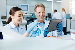 Positive delighted scientific couple looking at screen of the tablet Royalty Free Stock Photos