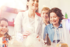 Positive delighted teacher showing her pupils different reagents Stock Photo