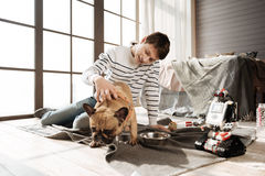 Positive delighted teenager putting right hand on the back of his dog stock photos