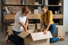 Positive delighted woman with braids helping her man. Packing things. Attentive bearded male person bowing head while looking downwards and helping to his Royalty Free Stock Photography