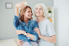 Positive delighted woman and her mother making selfies Stock Photography
