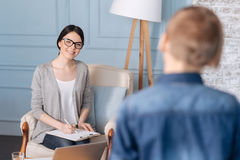 Positive delighted woman psychologist looking at her little patient. I am pleased. Attentive professional holding folder on her knees siting on the chair while Stock Images