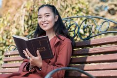 Positive delighted young female looking at camera. Reading with pleasure. Joyful brunette girl feeling happiness while holding favorite book in both hands stock images
