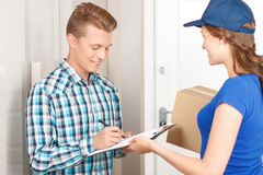 Positive deliverywoman delivering parcel Stock Photos