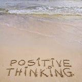 Positive denkende Mitteilung geschrieben auf Sand, mit Wellen in Hintergrund Lizenzfreie Stockfotos