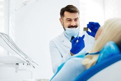 Positive dentist showing dental Xray image to the patient. Good results. Positive skilled dentist with a mask on his face standing in front of the patient while stock photography