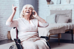 Positive disabled aged woman talking on smart phone at home. Full of joy. Merry old enable woman sitting in the wheelchair at home while smiling and using mobile Royalty Free Stock Photos