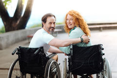 Positive disabled couple resting in the park. Happy couple. Positive smiling senior husband and wife bonding to each other and sitting in the wheelchairs while Royalty Free Stock Photo