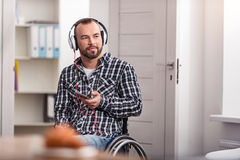 Positive disabled guy changing tracks. What is the next on my playlist. Attractive interested young man choosing songs using his smartphone while wearing his Royalty Free Stock Photos
