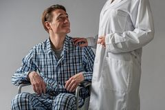 Positive disabled man in carriage supported by hospital worker. Young man with musculoskeletal disease sitting in wheelchair and smiling to nurse. She is holding Royalty Free Stock Image