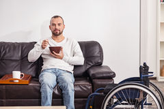 Positive disabled man having cereal in the living room. Promising start. Handsome relaxed handicapped guy enjoying his breakfast and morning coffee while sitting Royalty Free Stock Images