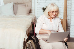 Positive disabled woman surfing the Internet. Modern granny. Pleasant delighted aged woman sitting in the wheelchair and using the Internet Royalty Free Stock Photos