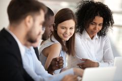 Positive diverse coworkers businesspeople sitting during briefing. Smiling multiracial millennial coworkers sitting together at desk in office with laptops royalty free stock photo