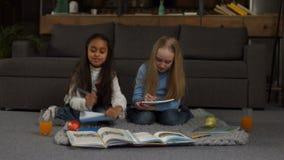Positive diverse girls doing homework together stock video footage