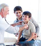 Positive doctor examining a little boy Stock Photo