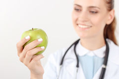 Positive doctor holding green apple Stock Photo
