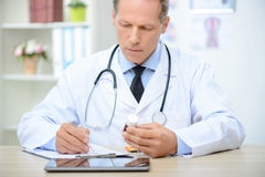 Positive doctor holding pills Stock Photo