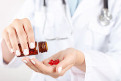 Positive doctor holding pills Stock Photos