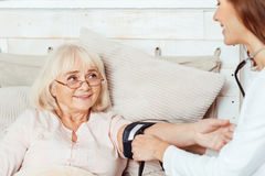 Positive doctor measuring blood pressure of her patient Royalty Free Stock Photos