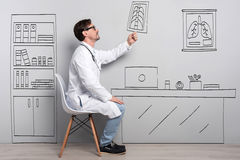 Positive doctor sitting on the chair Royalty Free Stock Photos