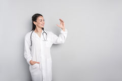 Positive doctor standing  on grey background Royalty Free Stock Image