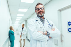 Positive doctor standing in hospital hallway Royalty Free Stock Photography