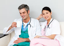 Positive doctors relaxing and drinking coffee Stock Image