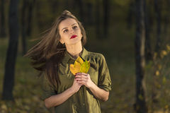 Positive dreamy autumn look. Positive autumn look. A dreamy looking teenage girl is looking up in an autumn forest while holding yellow leaves in her hands. Her Royalty Free Stock Image