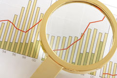 Positive Earning. A magnifying glass focusing on a positive earning chart Stock Photo